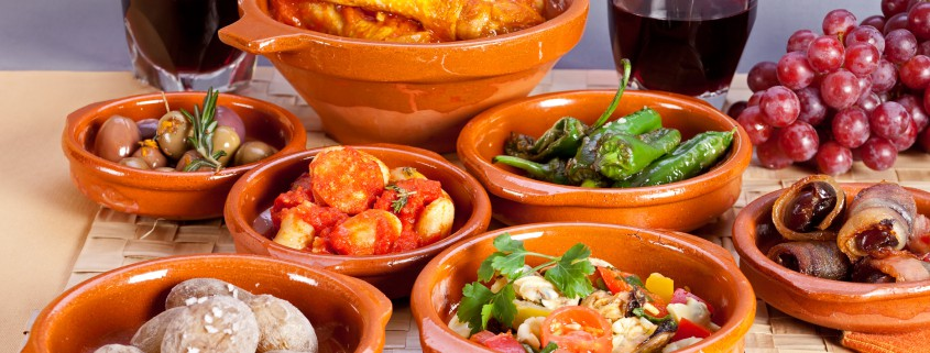 Collection of spanish tapas foods in terracotta bowls.